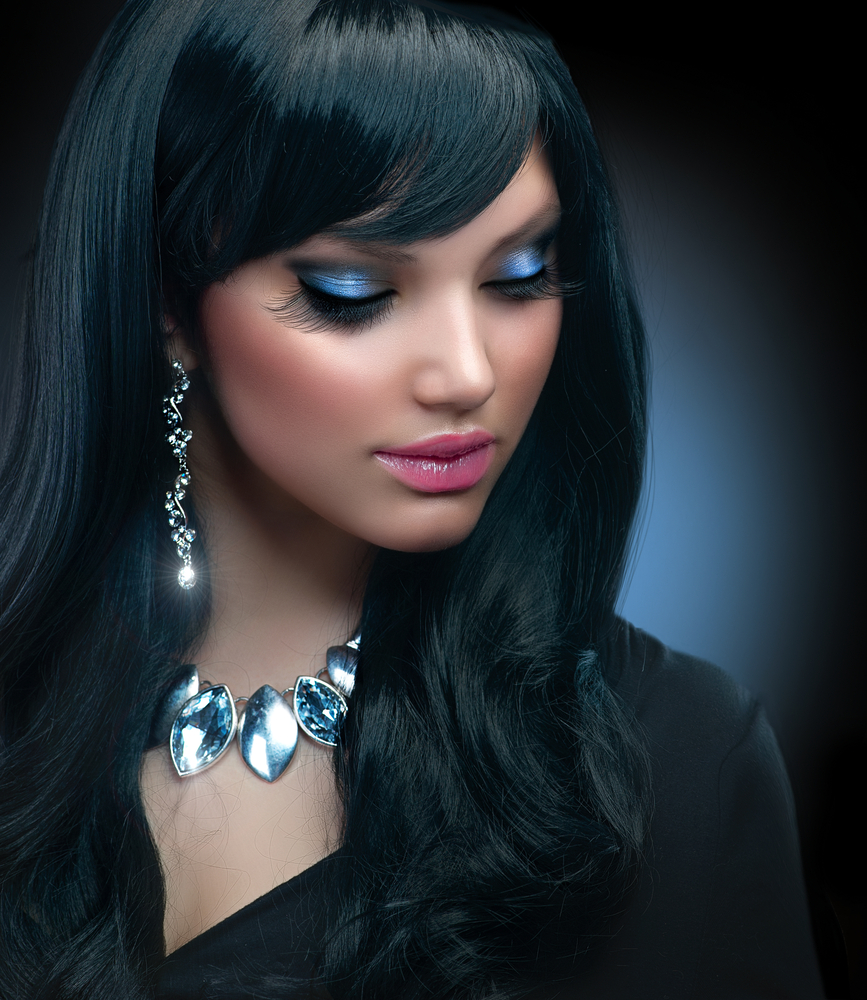 A woman on a dark background with dark hair, makeup and accessories