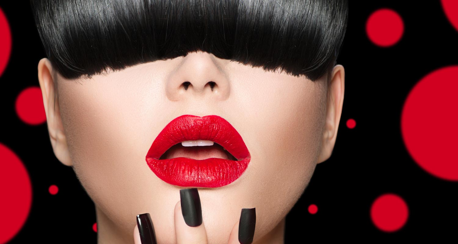 Woman with black hair and nails and long bangs that make her red lipstick pop