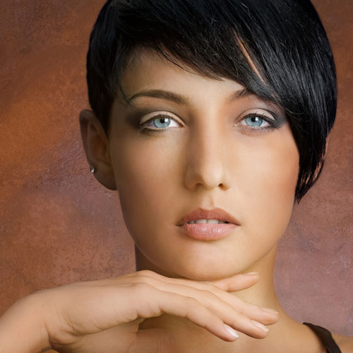 short haired woman caresses her chin