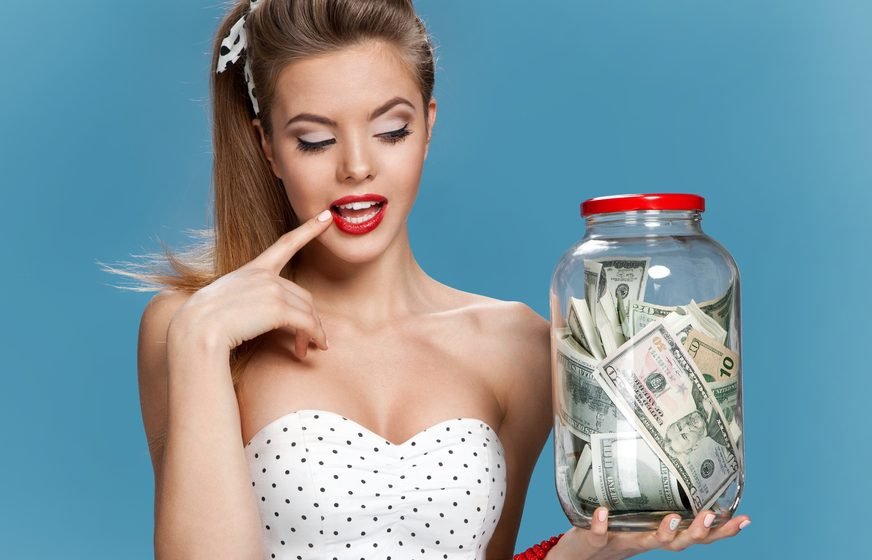 Pretty woman with jar of money looking at it curiously.
