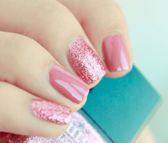 The nails of a woman, painted with pink and glitter