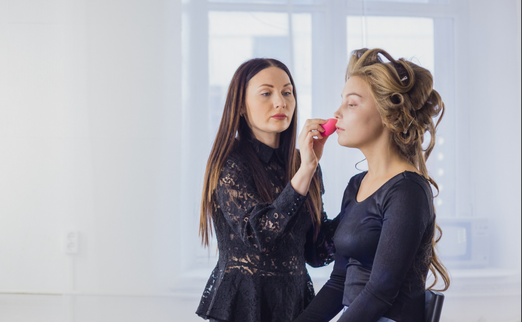 pretty asian woman doing makeup on a blonde with rollers in her hair