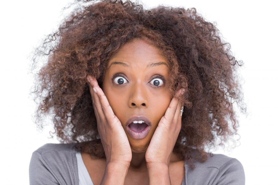 African American woman with natural hair looking surprised.