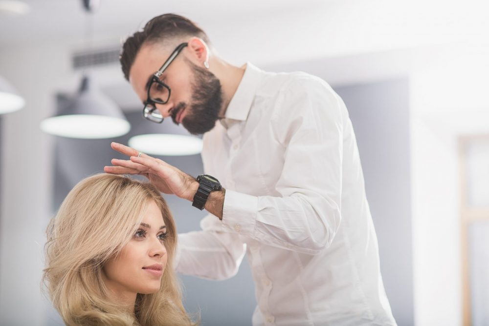 man giving a woman a haircut and style