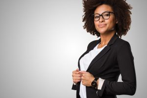 woman black with glasses and curly hair adjusting black business suit coat