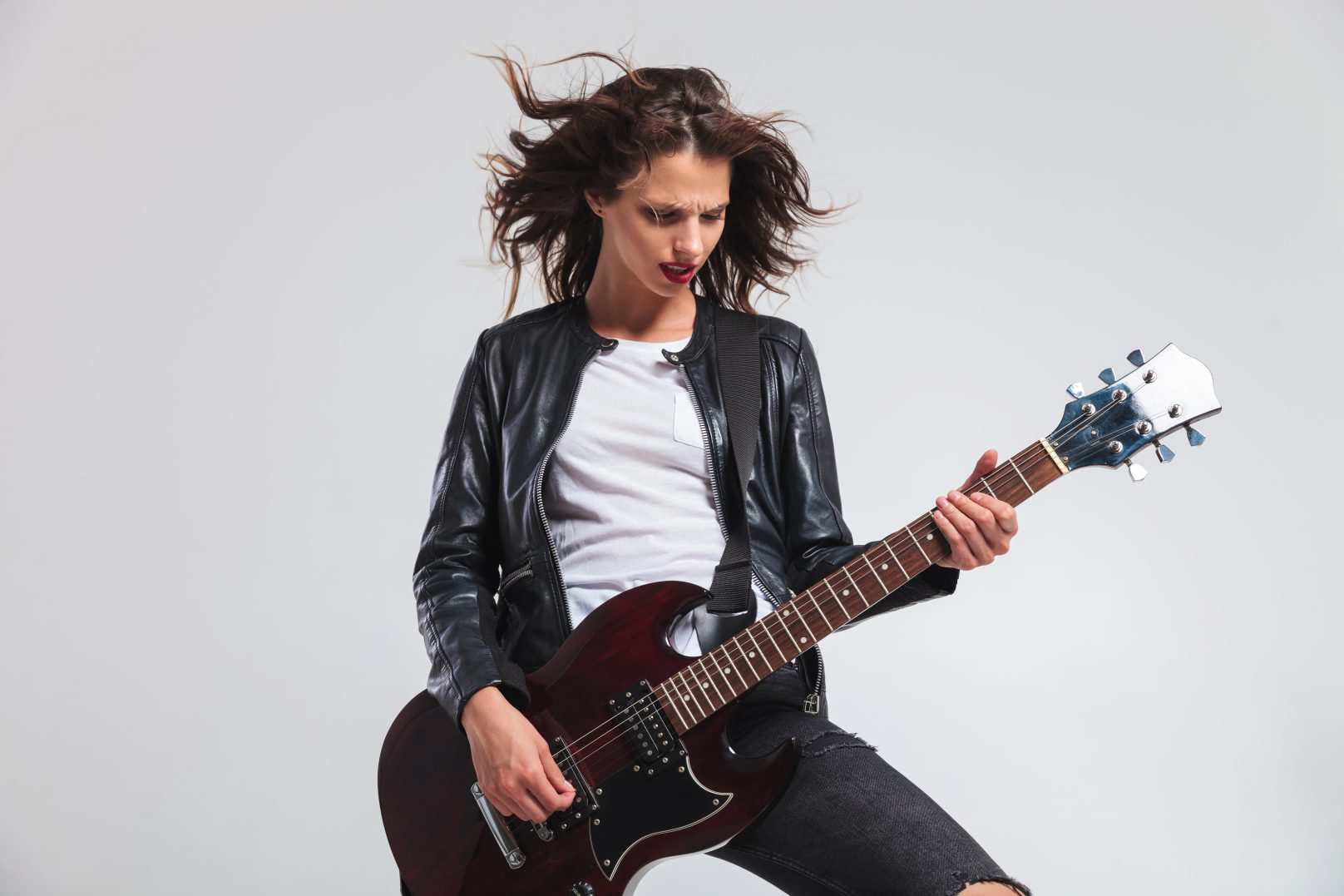 woman with brown flying hair and white shirt playing guitar