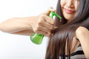 women putting hair serum into her hair