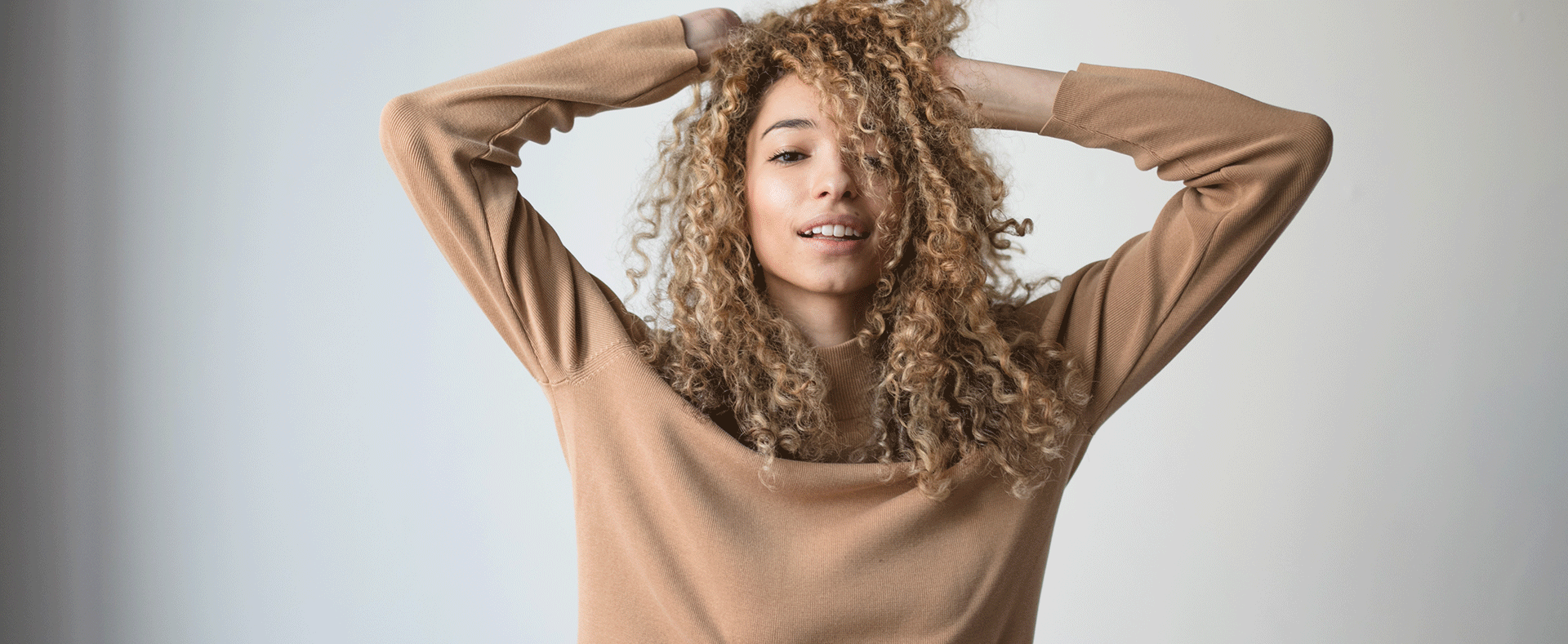 Woman in a brown sweater with curly blonde/brown hair.